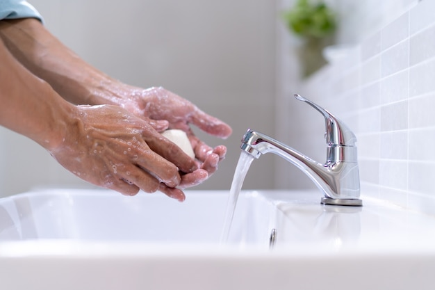 細菌の拡散を防ぐために、浴室の流しの前で石鹸ときれいな水で手を洗う男性。石鹸で手を洗う。