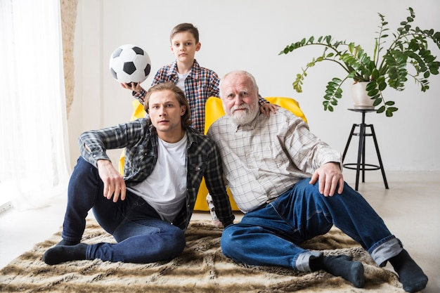 Men watching football sitting on carpet at home
