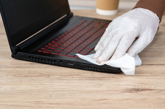 Men wear white gloves, use alcohol and spay cloth to clean their laptops to prevent viruses.