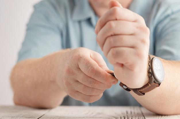 白に黒の革ストラップが付いた黒の時計を身に着けている男性
