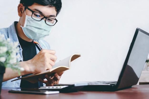 カジュアルな服装でマスクを着用している男性がオフィスで金融ビジネスの事務処理をチェックして分析します
