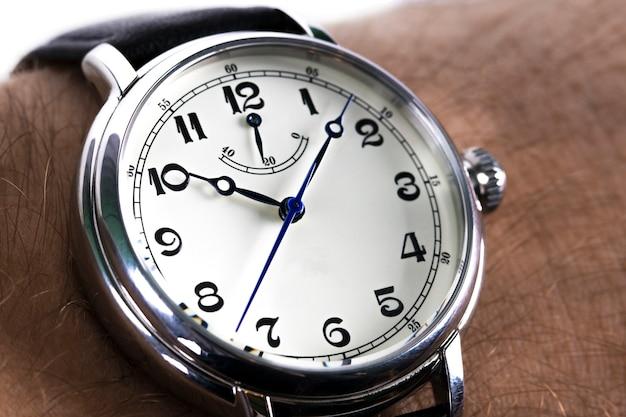 흰색 위에 검은 가죽 끈으로 시계를 착용하는 남자