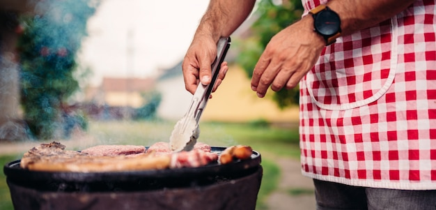 Men wearing apron barbecuing chicken meat