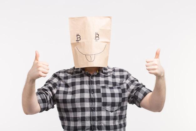 親指を立ててビットコインのシンボルと面白い紙のマスクを身に着けている男性