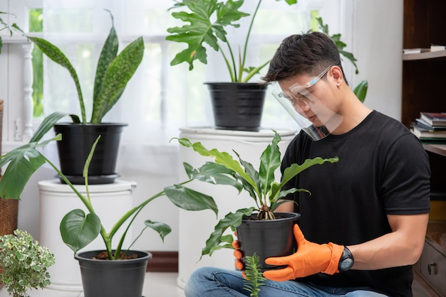 Men wearing orange gloves and planting trees indoors.