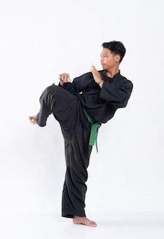グリーンベルト付きのプンチャックシラットのユニフォームを着た男性は、キックから防御的な脚の動きを実行します