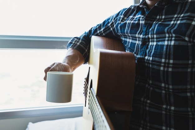 Men wearing a plaid shirt holding a coffee mug after playing the guitar