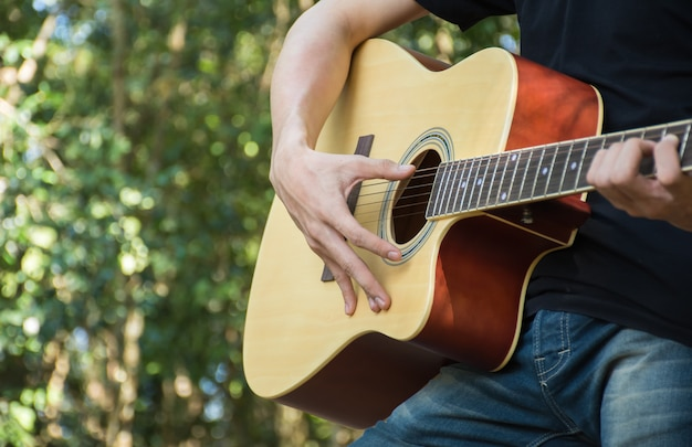 The men were caught playing guitar chords relaxing holiday amid fresh surrounded forest