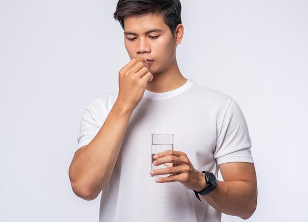 病気で抗生物質を服用しようとしている男性