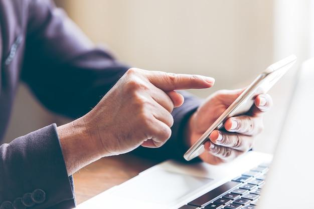 電子メールを作成および送信するスマートフォンを使用する男性は、メッセージを読み、webサイトでオンラインで製品を購入するのを支援します。ネットワーキングイベントインターネットオンライン、オンラインショッピングプラットフォーム