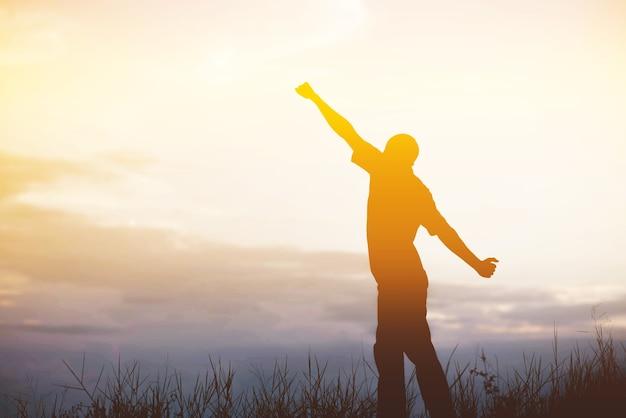 손을 들고 일출을 맞이하고 풍경을 즐기는 남성.