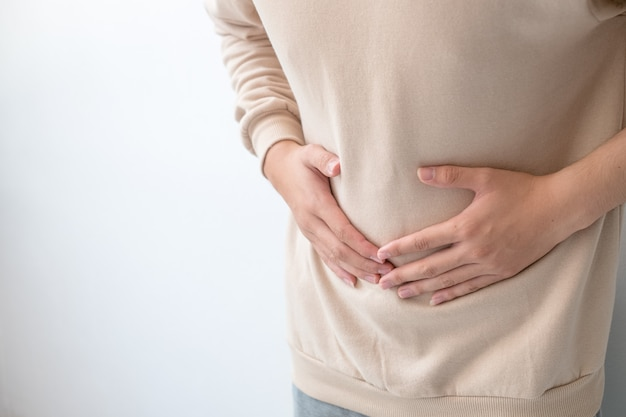 Men with abdominal pain standing, holding the body and hands photos