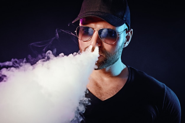 Men with beard in sunglasses vaping and releases a cloud of vapor