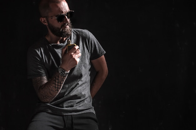 Men with beard in sunglasses vaping.