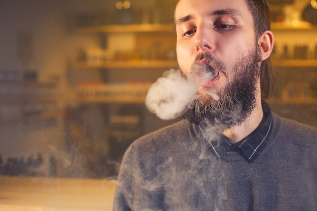 Men with beard vaping and releases a cloud of vapor