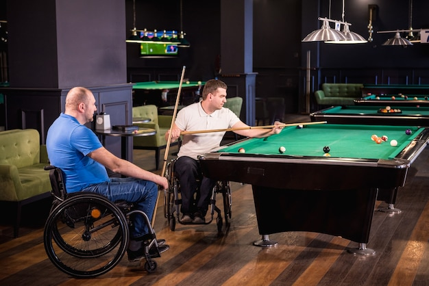 Men with disabilities in a wheelchair play billiards in the club