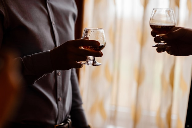 Men with a friend standing by the window. hold in the hands of glasses of whiskey.