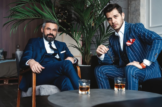 Men with a great style. two young handsome men in suits looking at camera while resting indoors.