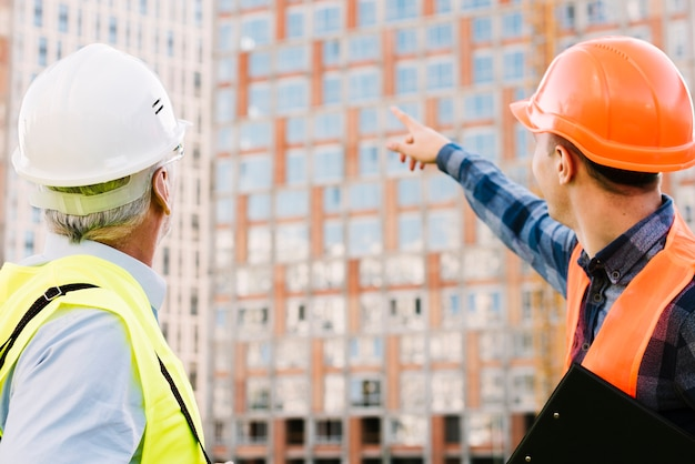 Men with helmets and safety vests looking at building