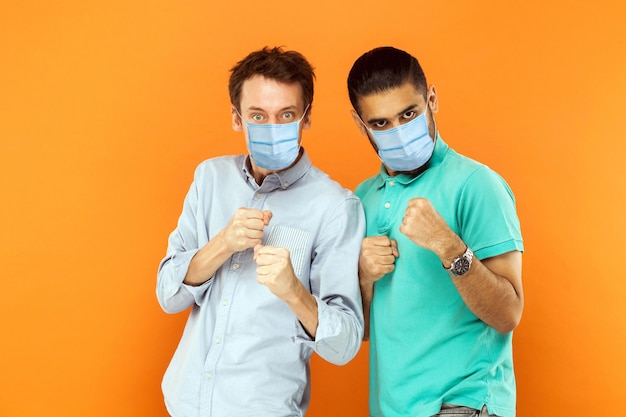 Men with mask standing with boxing fists and ready to attack or defence against virus or problem