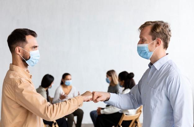 医療用マスクを持った男性が集団療法のセッションで拳をぶつけ合う