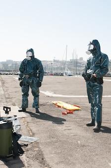 Мужчины в защитной одежде от вируса эбола или пандемии