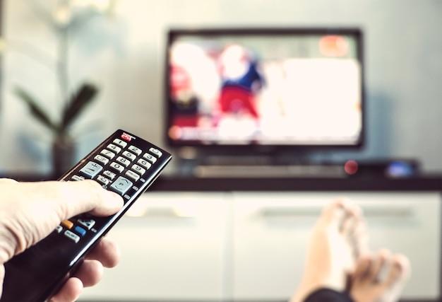 Мужчины с пультом дистанционного управления перед телевизором. рука с пультом дистанционного управления направлена на телевизор. мужчина расслабляется и смотрит спорт по телевизору.