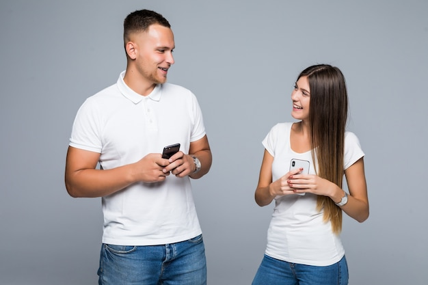 Coppia di uomini e donne in piedi con telefoni cellulari di marca nelle loro mani isolato su sfondo grigio
