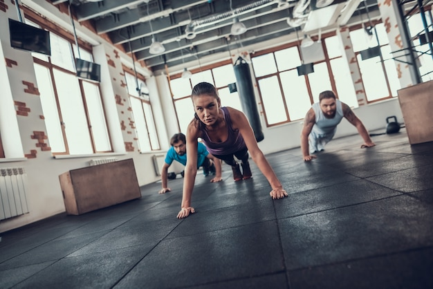 Men and woman doing push ups in the bright gym.
