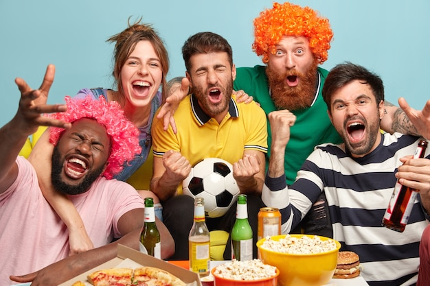 Men and woman fans watch football on tv at home, enjoy exciting game, clench fists, celebrate victory, express positive emotions, have popcorn in bowls, eat pizza, pose over blue wall.