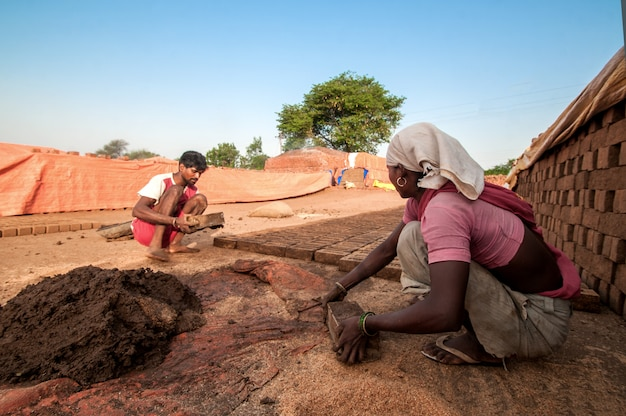 Men and woman making in traditional bricks of clay in brick factory