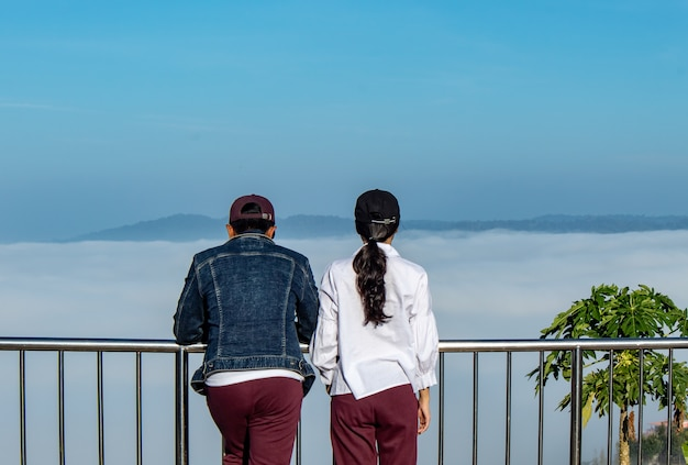Men and women are watching the fog on the mountain.