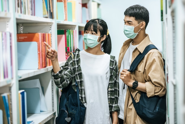 Uomini e donne che portano uno zaino e cercano libri nella biblioteca.