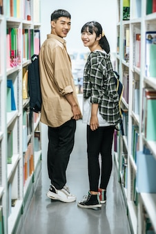 Men and women carrying a backpack and searching for books in the library.