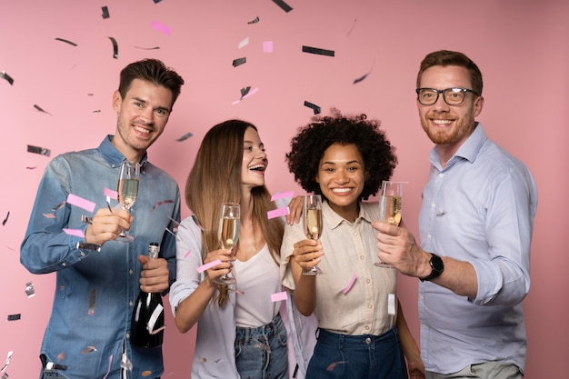 Men and women celebration with champagne glasses and confetti