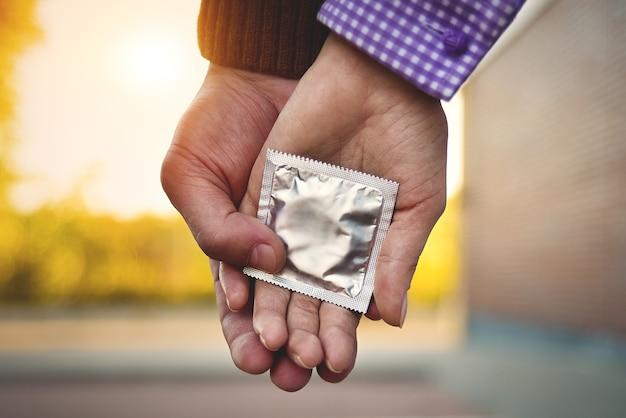 男性、女性、カップル自己防衛のためにコンドームを持っています。避妊を防ぐためのコンセプト。