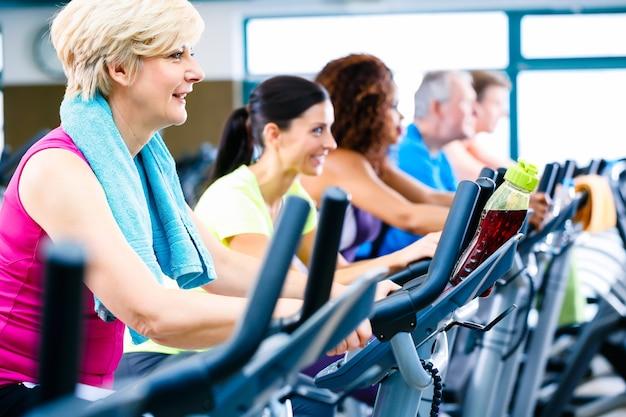 Men and women doing fitness spinning for sport