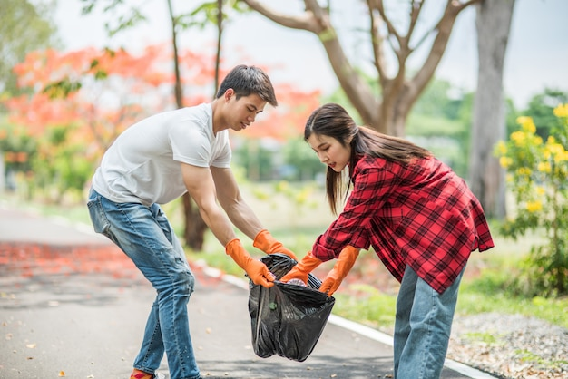 Men and women help each other to collect garbage.