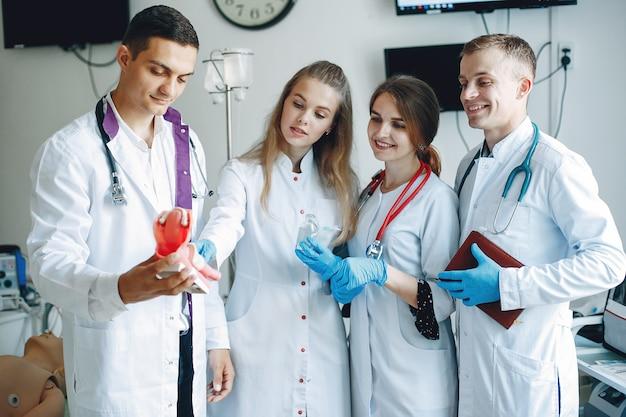 Uomini e donne in camici da ospedale tengono in mano attrezzature mediche