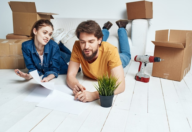 Men and women lie on the floor indoors with boxes of documents of flowers in a pot moving