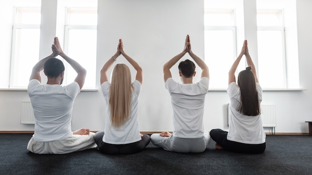 Men and women meditate on yoga classes. group of sporty people love doing in stretching training.