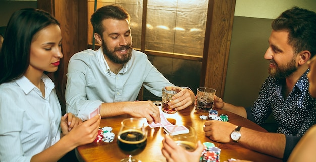 Men and women playing card game. poker, evening entertainment and excitement concept