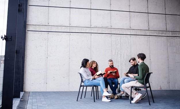Men and women sitting in a circle during group therapy, reading and talking.