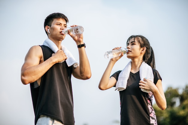 Men and women stand to drink water after exercise.