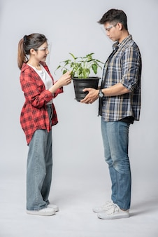 Men and women standing and holding plant pots in the house