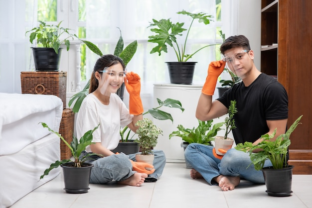 Men and women wearing orange gloves sat and planted trees in a house.