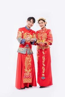 Uomini e donne che indossano qipao spendono soldi d'oro