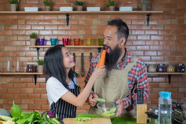 Men and women who tease each other while cooking in the kitchen with a red brick wall.
