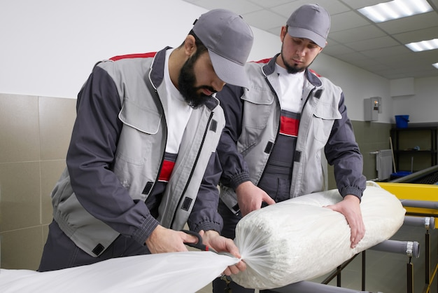 Men workers packing carpet in a plastic bag after cleaning it in automatic washing machine and dryer in the laundry service