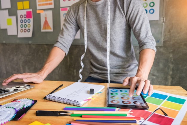 職場のスタジオでデジタルタブレットで衣料品のカラーチャートを選択するファッションデザイナーとして働く男性。